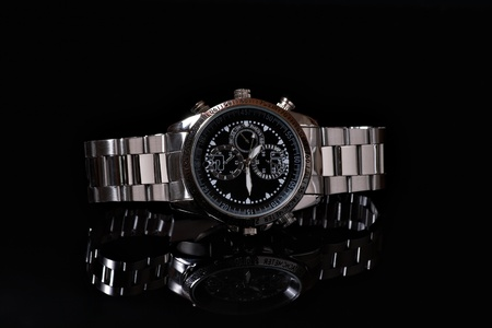 chronograph: Close up man wristwatch on the black background with reflection
