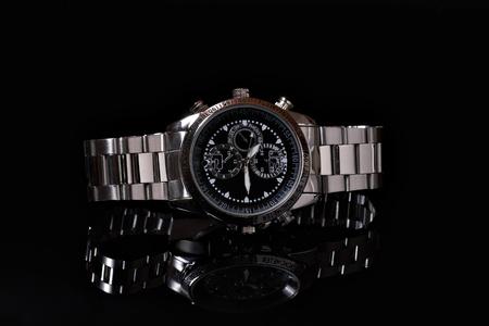 cronógrafo: Reloj de pulsera de hombre sobre el fondo negro con la reflexión de cerca