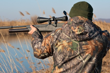 hunting rifle: Close up hunter aiming with weapon at the outdoor hunting Stock Photo