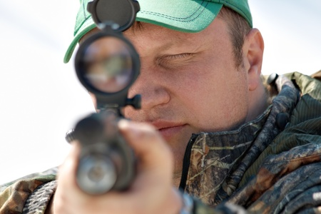 Close up hunter aiming with weapon at the outdoor hunting Stock Photo