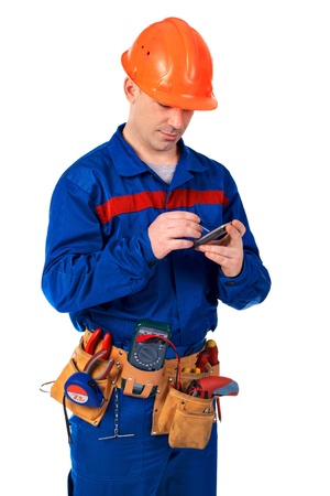 Worker in workwear with modern mobile phone against white  Stock Photo