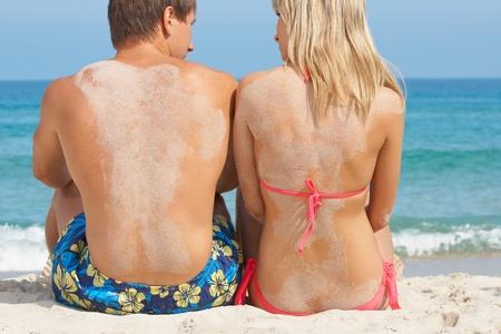 tun: Two young people on the beach near sea Stock Photo