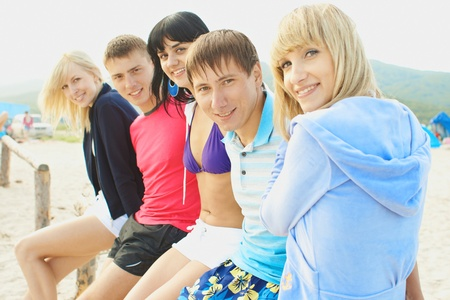 adult intercourse: Group young womans and boys model having fun on the beach Stock Photo