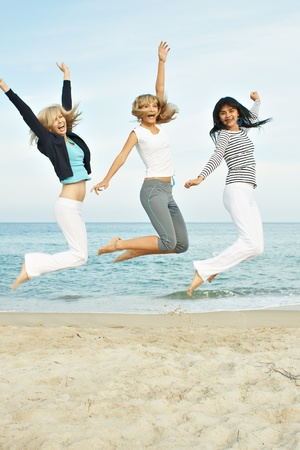 Three young girls jumping on the sea coast photo