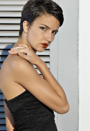 in vouge: Portrait young brunet model with short hair against wall Stock Photo