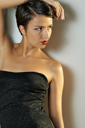 vouge: Portrait young brunet model with short hair against wall Stock Photo