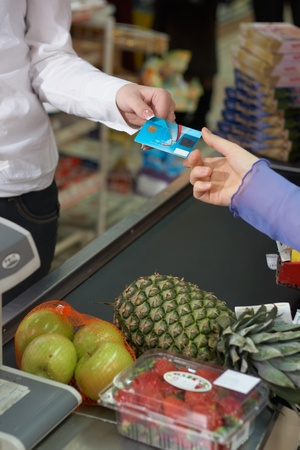 pay desk: Woman hand with debit card in shop for payment