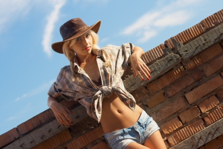 outdoor fashion portrait cowgirl in hat in the western village outdoor