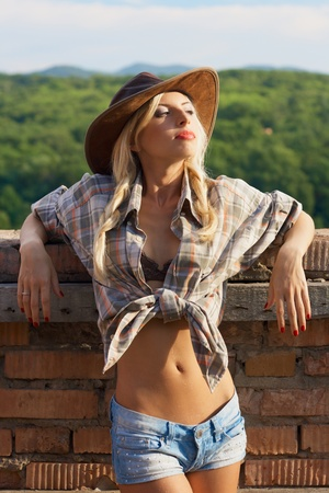 outdoor fashion portrait cowgirl in hat in the western village outdoor photo