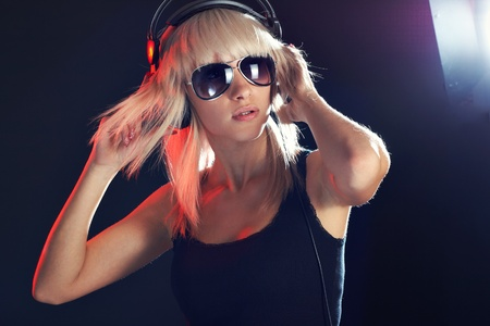 Young girl in dark in expression listening music photo