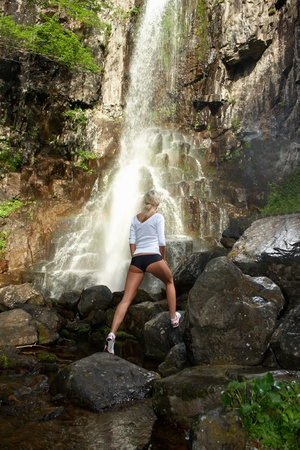 Young sporting girl walking outdoor near to waterfall photo