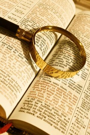 lupa: Zblízka Bible otevřenou stránku a lupu na to Reklamní fotografie