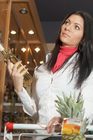 Young girl lookin choose alcohol botle in super market Stock Photo - 11595489