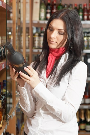 Young girl lookin choose alcohol botle in super market Stock Photo - 11595516
