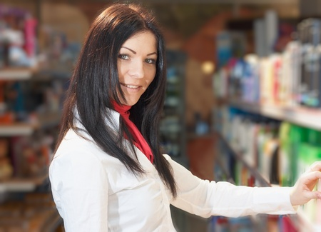 Young girl near counter choosing article in shop Stock Photo - 11595467
