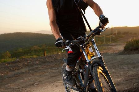 Evening outdoor sport shooting man with bike