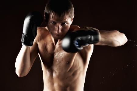 patada: Retrato boxeador de los deportistas, en estudio contra el fondo oscuro Foto de archivo
