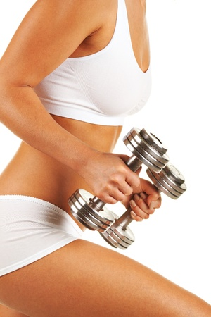 Young woman against white background with sporty body, with dumbbels