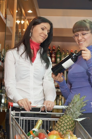 Two young woman looking vine botle in shop Stock Photo - 12269825