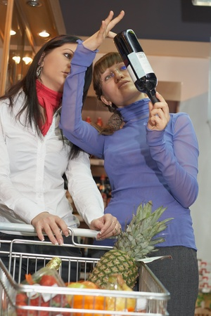 Two young woman looking vine botle in shop photo
