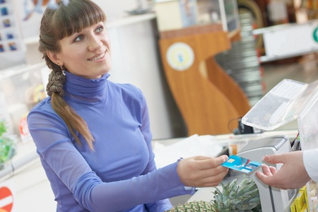 pay desk: Young girl payment debit card in shop Stock Photo