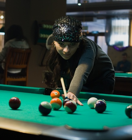 billiards tables: Young woman in billiard club playing in billiard