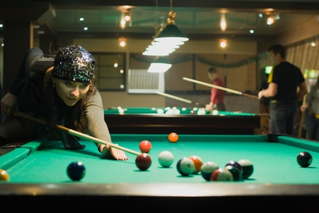 snooker tables: Young woman in billiard club playing in billiard