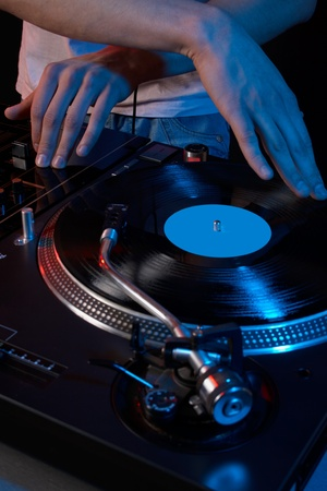 Close up acoustic vinyl player with dj hand photo
