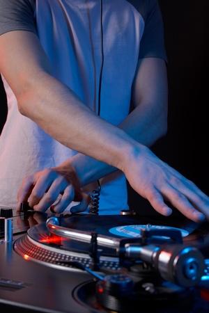 Jonge disk jockey voor thw vinyl schijven en mixer in club