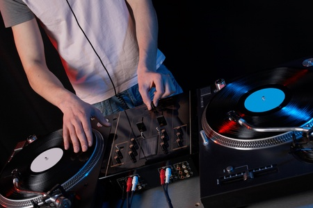 Young disk jockey for thw vinyl disks and mixer in club