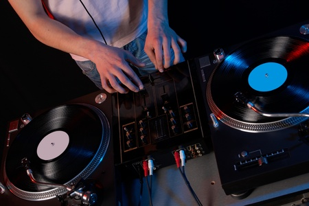 Young disk jockey for thw vinyl disks and mixer in club Stock Photo - 12624669