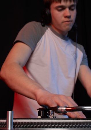 Young disk jockey for thw vinyl disks and mixer in club photo