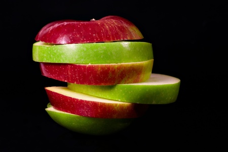 segment: Close up apple segment red and green against black background
