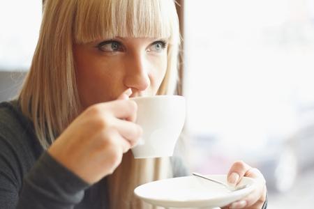 mujer tomando cafe: Mujer joven bebiendo café en la cafetería