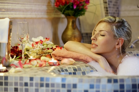Young woman in spa bathroom in bath with water 版權商用圖片