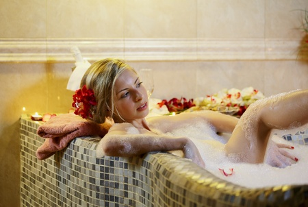 Young woman in spa bathroom in bath with water photo