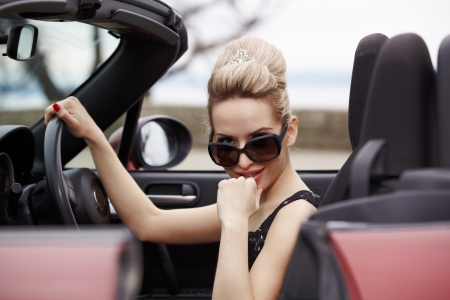 Woman and car cabriolet on the road Stock Photo