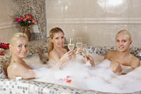 Three girls in hot whirlpool in spa centre party and\ communication