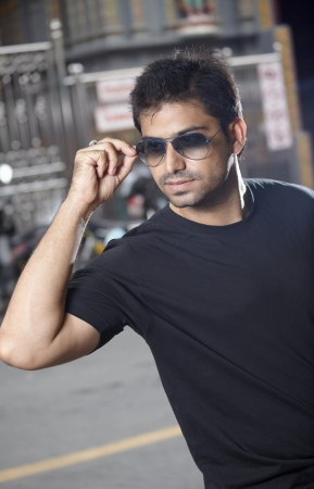 Portrait handsome indian man in sunglasses at the street Stock Photo
