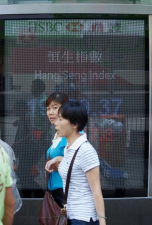 Hong-Kong - Hong-Kong, SEPTEMBER 2012, resident pedestrian people walking pass by information desk stock market. Hong-Kong, 11.09.2012