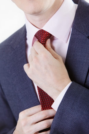 Close up businesman hands tie up tie against white photo