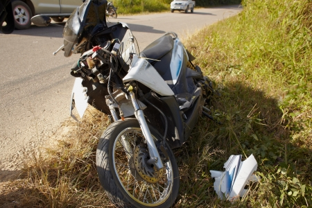 Crashed motorbike on the grass near highway road, after wreck