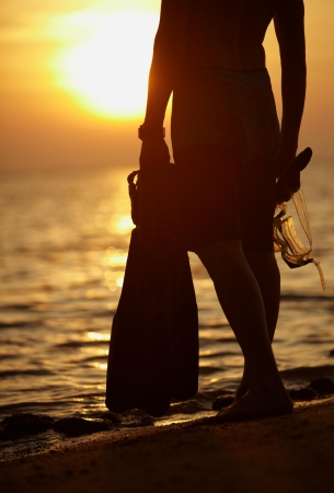 Man silhouette with scuba things near sea, against red sunlight