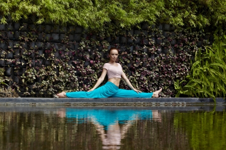 Young sporty woman in nature near water practice yoga photo