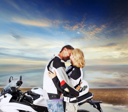 Couple two adult with motorcycle in riders clothes photo