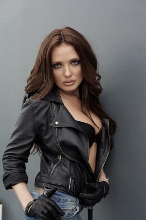 청바지와 회색 벽 근처 가죽 재킷에 젊은 여자 스톡 콘텐츠