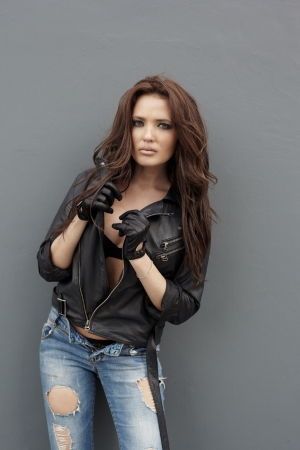 Young woman in jeans and leather jacket near gray wall Stock Photo