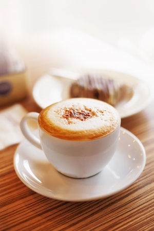 capuchino: Close up coffe cup with capuchino and cake in street cafe Stock Photo