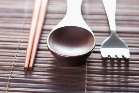 Close up kinchen ware spoon chopstick and fork on the wood mat photo