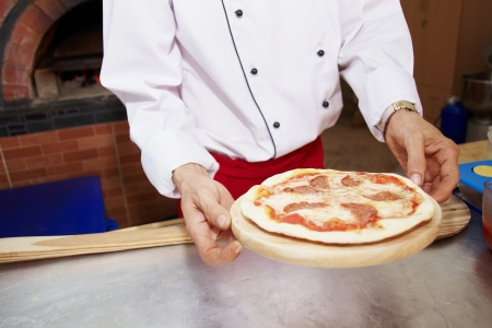Close up cooking italian pizza in small restaurant photo
